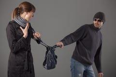 Man mugging woman Stock Images