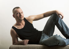 Man in muscle shirt lying on a sofa. Young man lying on a sofa, looking at the camera, muscle shirt and jeans, well maintained and built, portrait, three-day Royalty Free Stock Image