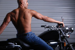 Man with muscular back. Back shot of a sexy muscular man sitting on a motor bike, wearing jeans and no shirt Royalty Free Stock Photos