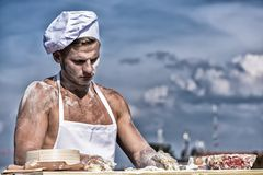 Man muscular baker or cook kneading dough in bowl. Bakery concept. Baker at working surface covered with flour, kneading