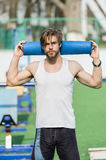 Man with muscular body, beard holding yoga or fitness mat Royalty Free Stock Images