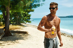Man With Muscular Body Drinking Healthy Drink On Beach. Summer Stock Photography