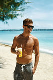 Man With Muscular Body Drinking Healthy Drink On Beach. Summer Royalty Free Stock Photos