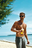 Man With Muscular Body Drinking Healthy Drink On Beach. Summer Royalty Free Stock Photo