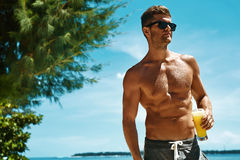 Man With Muscular Body Drinking Healthy Drink On Beach. Summer Stock Image