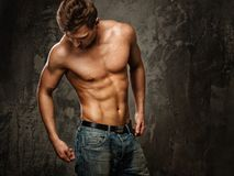 Man with muscular torso. Young man with muscular  body in blue jeans Royalty Free Stock Photo