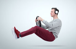 Man music fan in headphones drives a car with a steering wheel Royalty Free Stock Photos