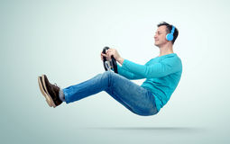 Man music fan in headphones drives a car with a steering wheel Royalty Free Stock Image