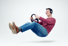 Man music fan in headphones drives a car with a steering wheel Royalty Free Stock Photo