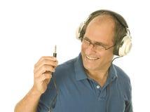 Man music head phones looking at plug Stock Images