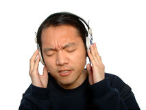 Man and Music.Isolated. One chinese man enjoying listening to music through his headphones.isolated Stock Images