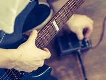 Man adjusting guitar effects pedal. Man with musical instrument setting up guitar audio stomp box effects and cables in music studio Royalty Free Stock Photography