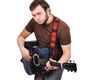 Man musician playing his guitar. Handsome young man musician playing his guitar Royalty Free Stock Photo