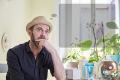 Man musing with a thought bubble over his head. Sitting in a kitchen indoors royalty free stock photos