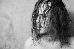 Black and white art monochrome photography. A man with a mustache and a beard with long wet hair on the background of gray walls, copyspace Royalty Free Stock Photos