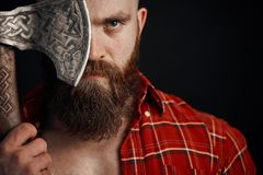 Man with mustache is holding a battle axe cover his eye and looking on camera on black background royalty free stock photos