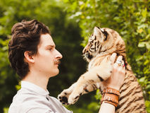 A man with a mustache looks into the face of a tiger cub. Otdoors Royalty Free Stock Image