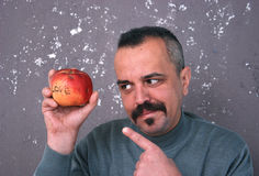 Man with mustaches showing on Valentine apple Royalty Free Stock Image