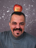 Man with mustaches with Valentine apple on a head Royalty Free Stock Images