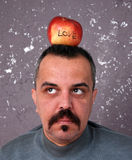 Man with mustaches with Valentine apple on a head Royalty Free Stock Photography