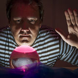Man with mystic sphere. A man in a striped shirt with a raised hand, behind a glass ball red illuminated Stock Photography