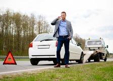 Man nära hans brutna bil på en vägren Arkivfoton