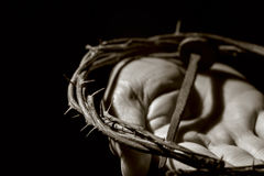 Man with a nail and a crown of thorns. Closeup of the hand of a young caucasian man with a nail of Jesus Christ and a crown of thorns, in black and white Stock Images