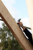 Man nailing a lath to a roof rafter Royalty Free Stock Photos
