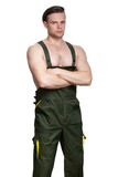 A man with a naked torso in dark green overalls Stock Image