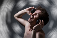 A man with a naked torso listening to music with headphones Royalty Free Stock Image