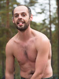 Man with naked torso showing tongue. On blurred background stock images