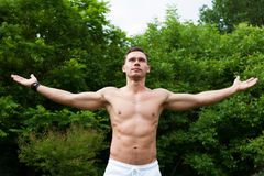 Man with a naked torso stands with his hands up Stock Images
