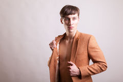 Man in naked torso wearing a fashion jaket. On gray background in studio photo Stock Photography
