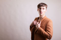 Man in naked torso wearing a fashion jaket. On gray background in studio photo Stock Photo