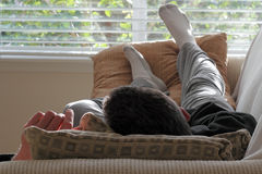 Man Napping on a Couch. Adult caucasian male laying with his head on a pillow on a couch with his feet up on some pillows in front of a bright living room window Royalty Free Stock Photos
