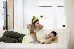 Man Napping On Sofa With Daughter Leaning Over Royalty Free Stock Photos