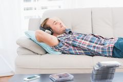 Man napping on sofa with music Stock Photos