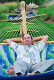 Man Naps on Hammock. A mature man rests on a hammock while on vacation in South Carolina Royalty Free Stock Photography