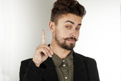 Man narrowed his eyes and raised his index finger Stock Photo