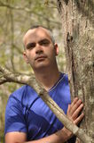 Man in nature. This picture represents the man dressed with a blue v-neck t-shirt leaning against a tree. He has a serious expression while looking the nature Stock Image