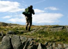 Man in nature. A man walking with backpack out in the wilderness Stock Photos