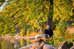 Man in nature. Adult man sitting under the tree, resting. Early fall trees, lake water and soft sunset light Stock Images