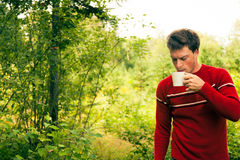 Young man in nature with a mug of coffee Royalty Free Stock Image