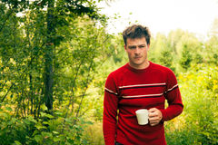 Young man in nature with a mug of coffee Stock Photography