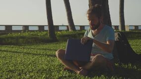 Man in nature park sitting with laptop under a palm tree. Freelancer completes work and closes laptop in slow motion stock video