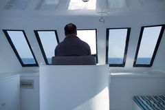 Man navigating a boat Stock Images