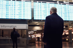 Man near airline schedule Royalty Free Stock Photos