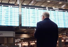 Man near airline schedule. Back view of adult man wearing black coat, holding tickets and passport in hand, checking flight timetable in international airport Stock Photography