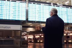 Man near airline schedule. Back view of adult man wearing black coat, holding tickets and passport in hand, checking flight timetable in international airport Stock Photos