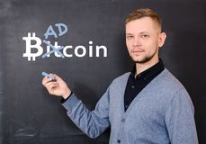 Man near a black school board on which is written bitkoin, part of the word Bitcoin is replaced by Bad. The concept of unreliability and instability of bitcoin stock photo